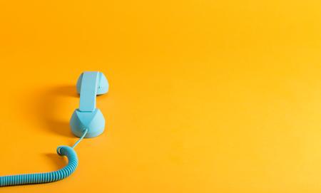 Vintage téléphone bleu combiné de téléphone sur un fond jaune Banque d'images - 83084791