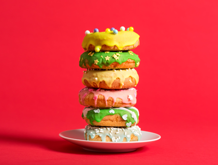 Colorful glazed donuts on a bright red background