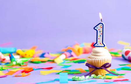 Eerste thema van de verjaardagsviering met cupcake kaars en feestartikelen