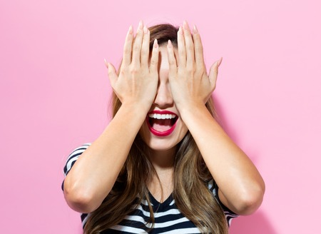 disbelief: Young woman covering her eyes with her hands