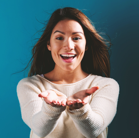 Happy woman showing or offering something with her hands