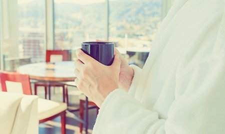 Young man in a bathrobe with a cup of coffee in a brightly lit modern interior room 版權商用圖片