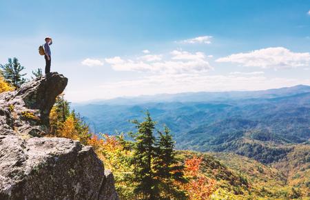 Man aan de rand van een klif met uitzicht op de bergen hieronder