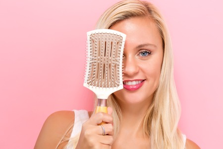 Beautiful woman holding a hairbrush on a pink background