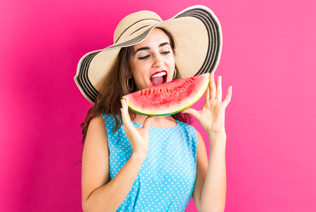 Happy young woman holding watermelon on a pink background