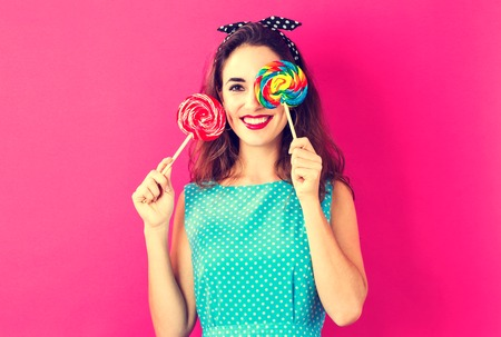 Mulher jovem, segurando, pirulitos, ligado, um, cor-de-rosa, fundo Foto de archivo - 83302268