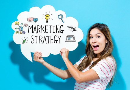 Marketing Strategy text with young woman holding a speech bubble on a blue background