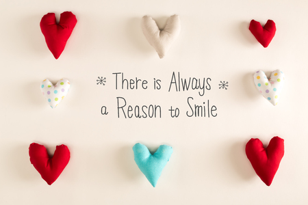Ther Is Always A Reason to Smile message with blue heart cushions on a white paper background Stock Photo