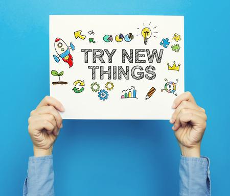 Probeer New Things-tekst op een witte poster op een blauwe achtergrond Stockfoto