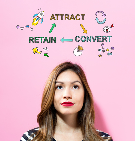 Attract Convert Retain text with young woman on a pink background Imagens