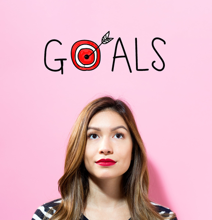 Goals text with young woman on a pink background Stock Photo