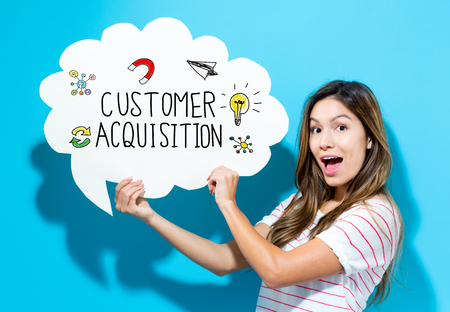 Customer Acquisition text with young woman holding a speech bubble on a blue background Stock Photo