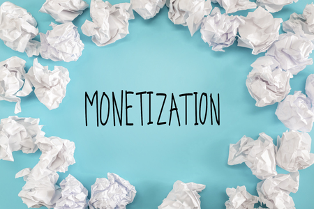 Monetization text with crumpled paper balls on a blue background Banco de Imagens