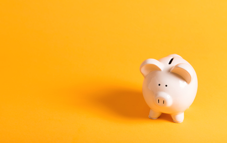 White piggy bank on yellow