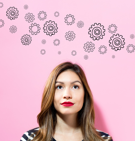 Gears with young woman on a pink background