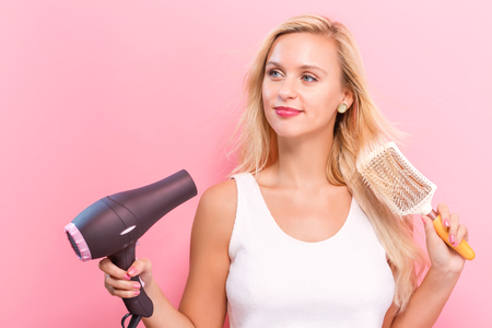 hairdryer: Beautiful woman holding a hairdryer on a pink background
