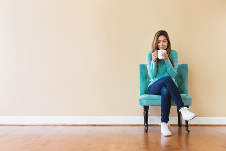 Young latina woman drinking coffee while sitting