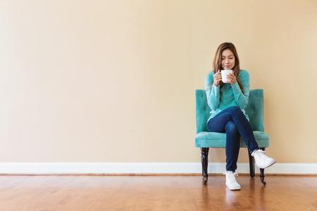 Une jeune femme latinoise boit du café en train de s'asseoir Banque d'images - 83662062