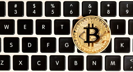 Gold bitcoin cryptocurrency with a latop keyboard Stock Photo