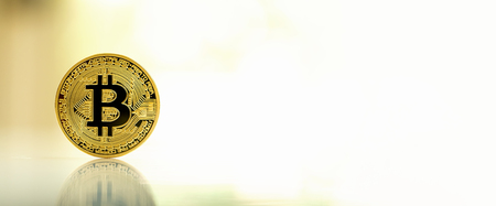 Gold bitcoin cryptocurrency on reflective table with bright background Zdjęcie Seryjne