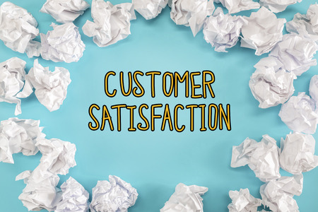 Customer Satisfaction text with crumpled paper balls on a blue background Banco de Imagens