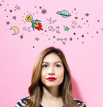 Idea Rocket with young woman on a pink background