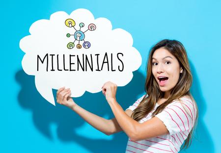 Millenials-tekst met jonge vrouw die een toespraakbel op een blauwe achtergrond houdt Stockfoto