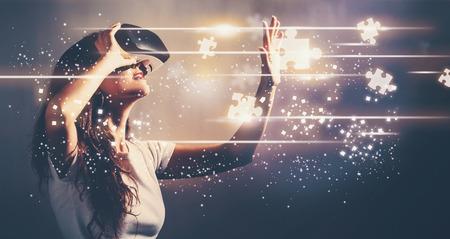 仮想現実のヘッドセットを使用して若い女性とパズルします。 写真素材