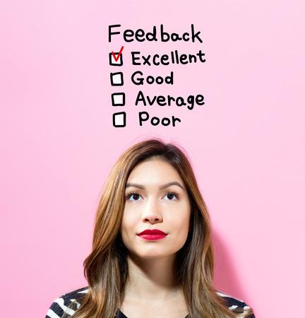ピンクの背景の若い女性とフィードバック本文