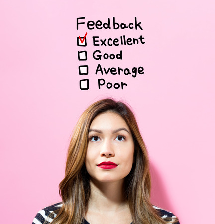 Feedback text with young woman on a pink background Stock Photo