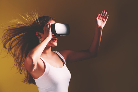 futuristic girl: Happy young woman using a virtual reality headset