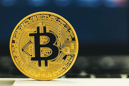 Gold bitcoin cryptocurrency with a latop computer Stock Photo