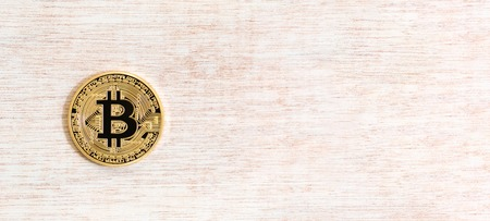 Gold bitcoin cryptocurrency on a wooden table Zdjęcie Seryjne