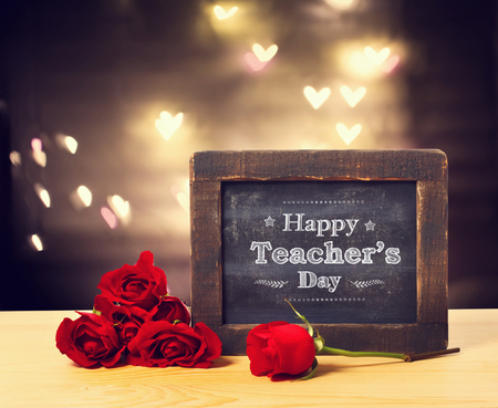 Happy Teachers day message on a small chalkboard with red roses