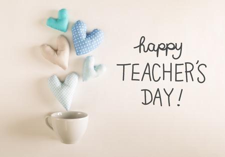 Mensagem do dia dos professores com almofadas de coração azul saindo de uma xícara de café Foto de archivo - 84045142