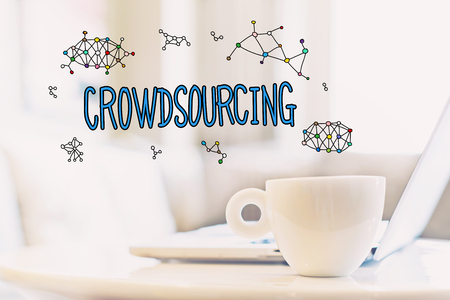 Crowdsourcing concept with a cup of coffee and a laptop