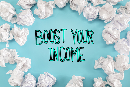 Boost Your Income text with crumpled paper balls on a blue background
