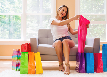Young woman with many brightly colored shopping bags in her living room Stock Photo