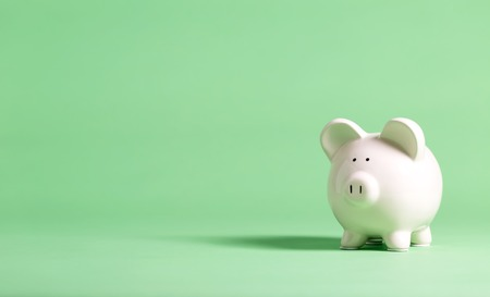 White piggy bank with glasses on a muted green background Archivio Fotografico