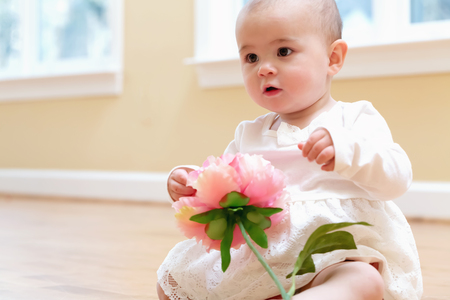 Toddler girl with a big flower in a white dress