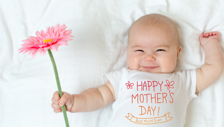 Mother's Day message with baby girl holding a flower Standard-Bild