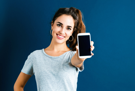 Young woman using her phone on dark blue background