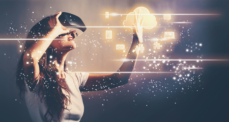 Colud Computing with young woman using a virtual reality headset Stock Photo