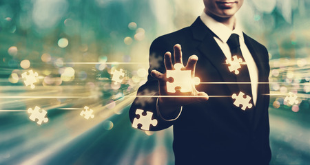 Puzzle pieces with businessman on blue tech background Stock Photo