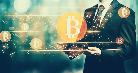 Bitcoins with man holding a tablet computer