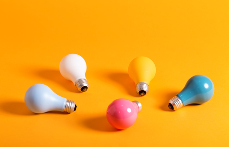 Colored light bulbs in arranged on a yellow background