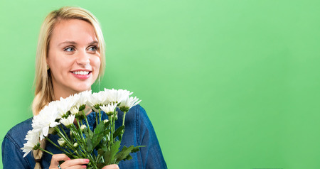 Young woman with flowers on a green background Stock Photo