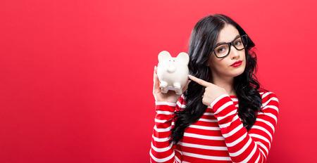 Giovane donna con una banca piggy su uno sfondo rosso