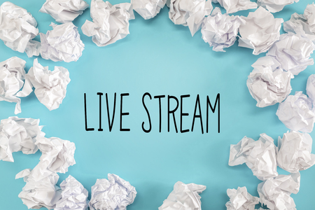 Live Stream text with crumpled paper balls on a blue background