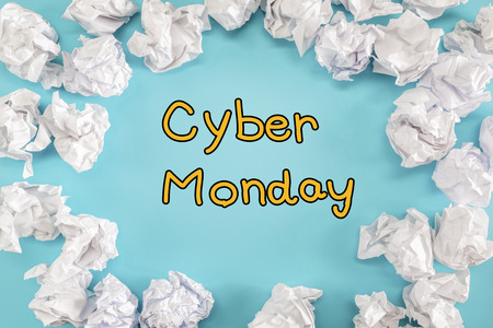 Cyber Monday text with crumpled paper balls on a blue background